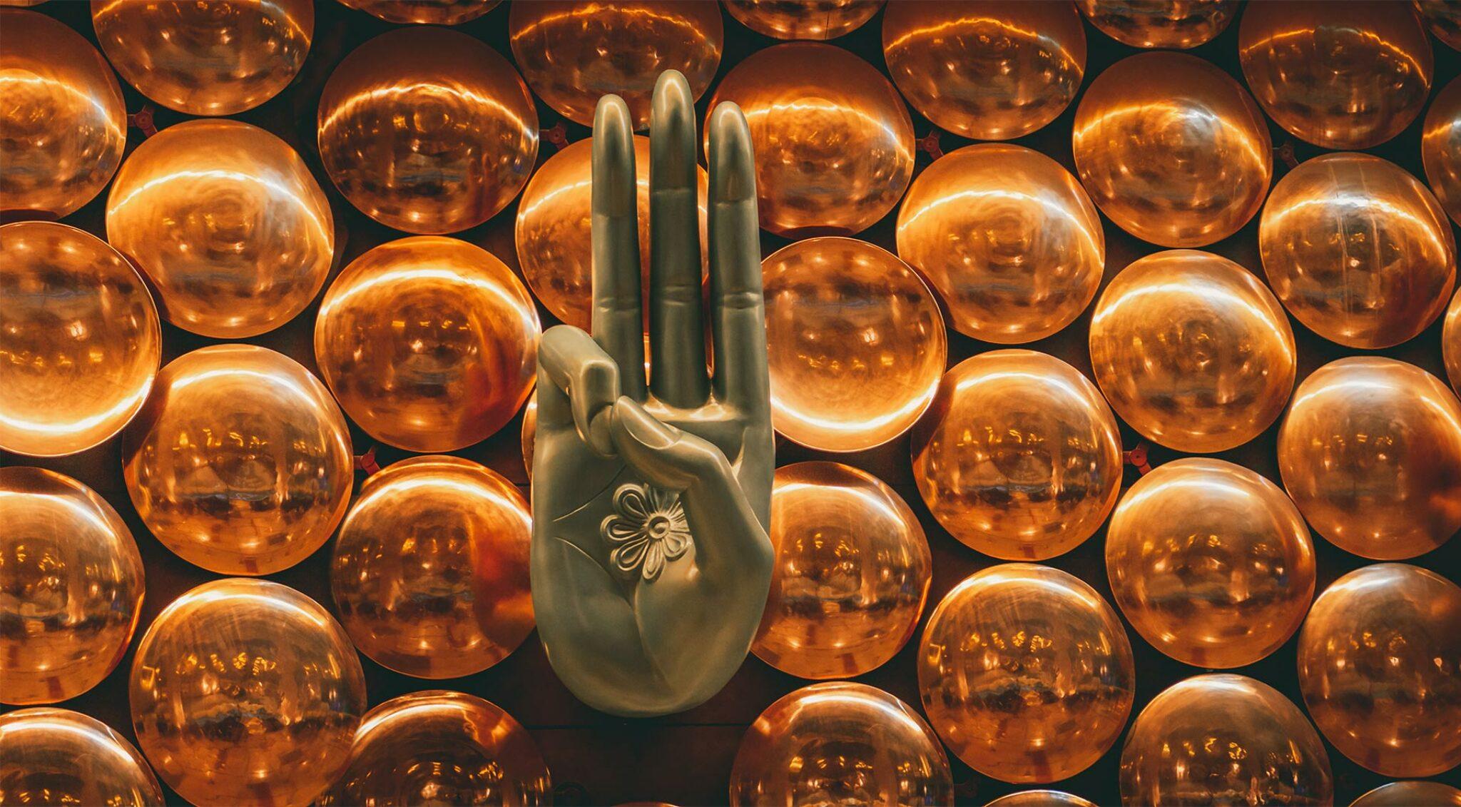 Hand aus Gold in Meditationshaltung.