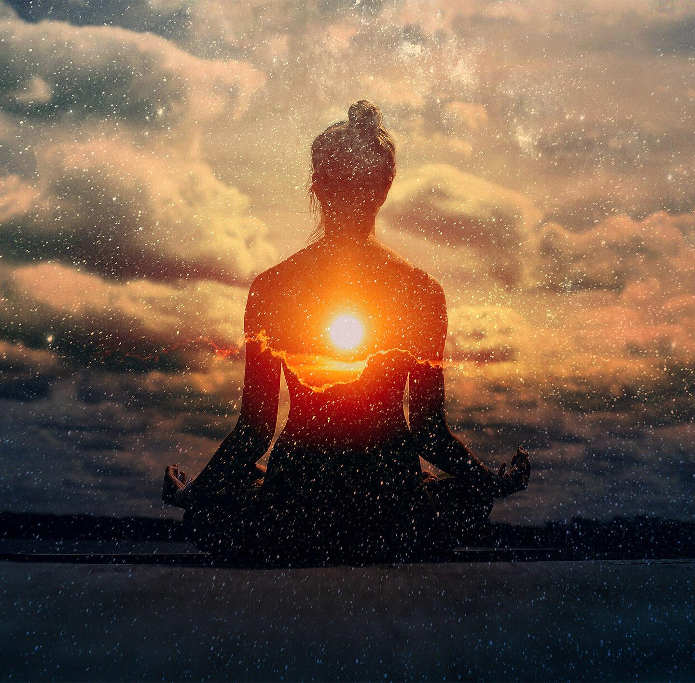 Frau meditiert im Lotussitz vor einem Sonneruntergang.