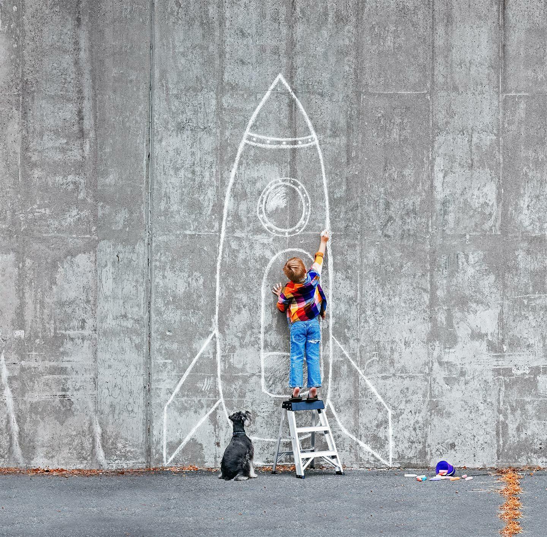 Mit Kreise malt ein Junge eine große Rakete an eine graue Wand.